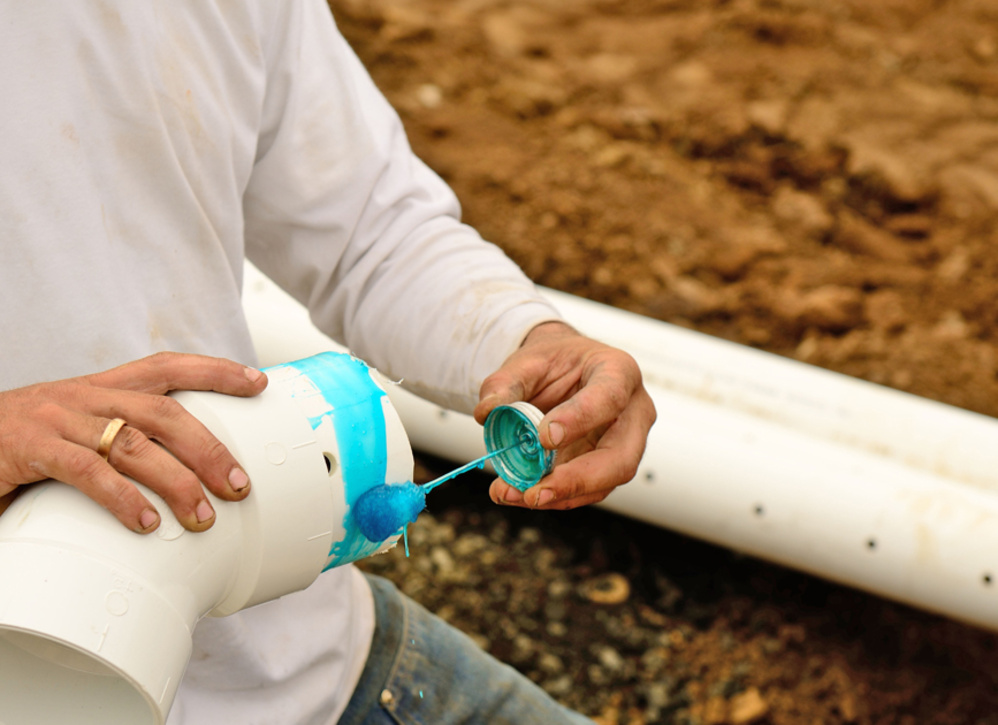 Worker applying blue adhesive to piping