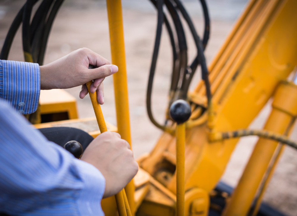Worker pulling lever of heavy machinery